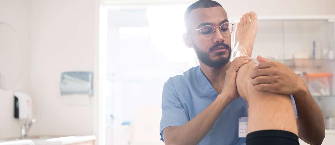 Ein männlicher Therapeut bietet Hilfe bei Arthrose während der Behandlung des Knies eines Patienten
