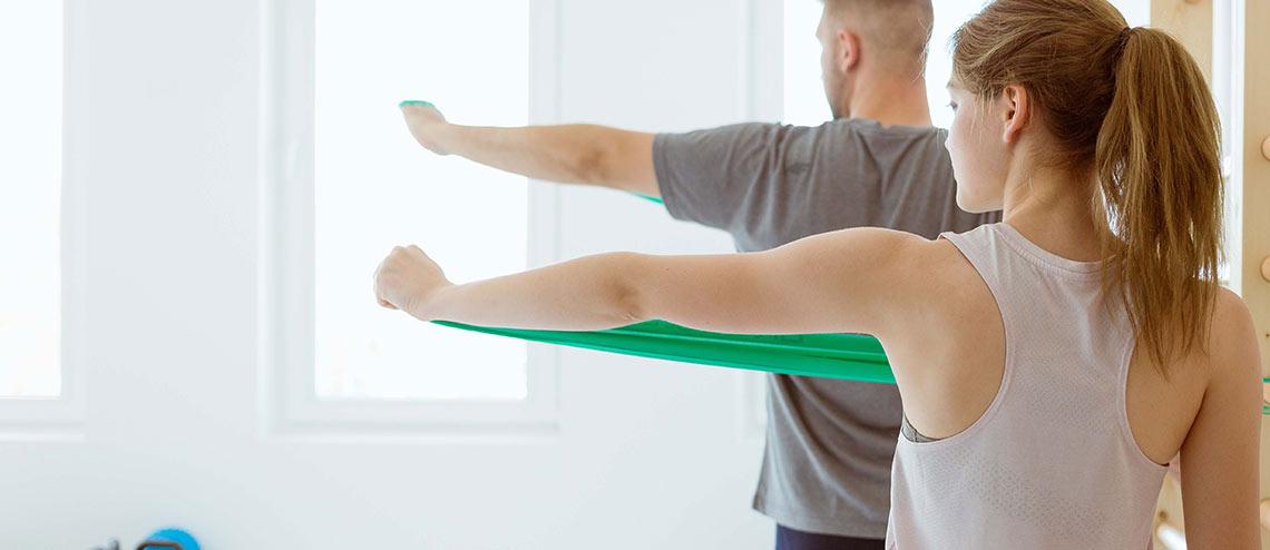 Eine Frau und ein Mann führen Gymnastik Übungen mit einem Gymnastikband zur Kräftigung der Schulter bei Arthrose aus.