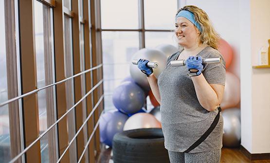 Eine übergewichtige Frau treibt Sport zur Gewichtsabnahme und Entlastung der Gelenke bei Arthrose