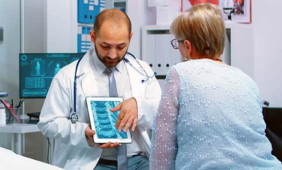 Ein Orthopäde erklärt einer Patientin anhand eines Röntgenbilds die Arthrose Diagnose